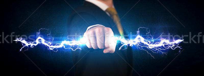 Stock photo: Business man holding electricity light bolt in his hands