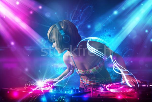 Energetic Dj girl mixing music with powerful light effects Stock photo © ra2studio