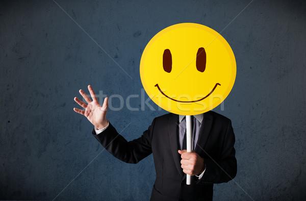 üzletember tart mosolygós arc emotikon citromsárga fej Stock fotó © ra2studio