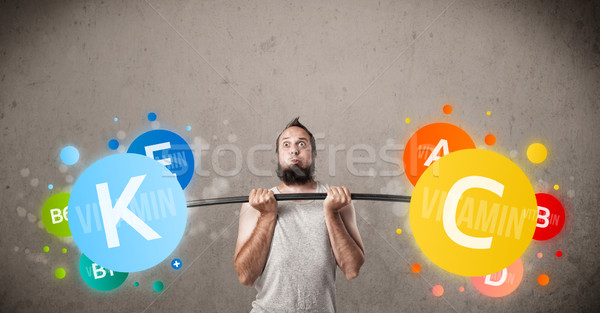 skinny guy lifting colorful vitamin weights Stock photo © ra2studio