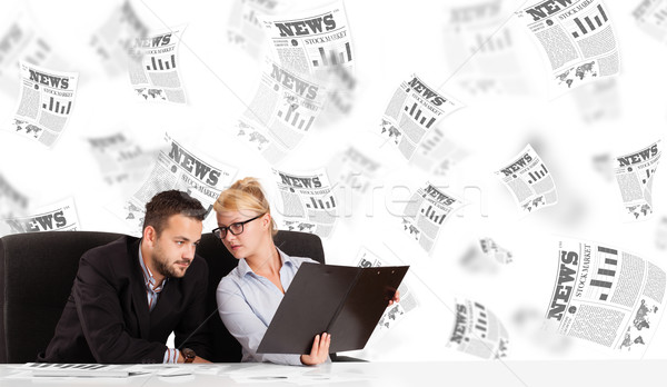 Business man and woman at desk with stock market newspapers Stock photo © ra2studio