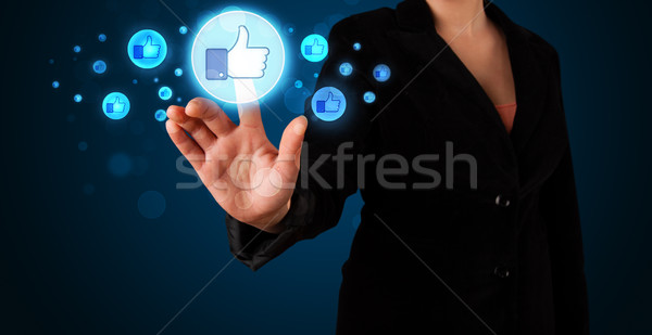Young businesswoman pressing thumbs up button on modern social n Stock photo © ra2studio