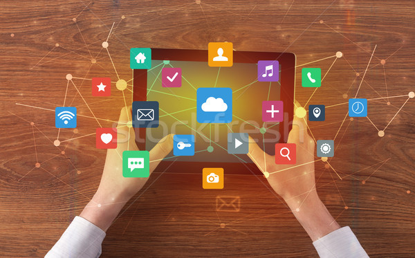 Hand using multitask tablet with application symbols and icons concept Stock photo © ra2studio