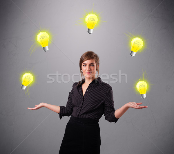 young lady standing and juggling with light bulbs Stock photo © ra2studio
