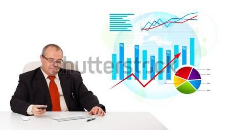 Businessman sitting at desk with statistics Stock photo © ra2studio