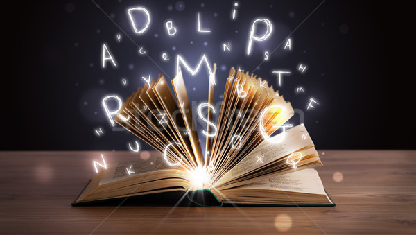 Open book with glowing letters flying out Stock photo © ra2studio