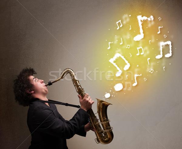 Jóképű zenész játszik szaxofon hangjegyek fiatal Stock fotó © ra2studio