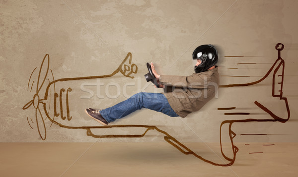 Funny pilot driving a hand drawn airplane on the wall Stock photo © ra2studio