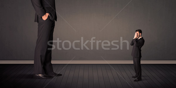 Little bussinesman in front of a giant boss legs concept Stock photo © ra2studio