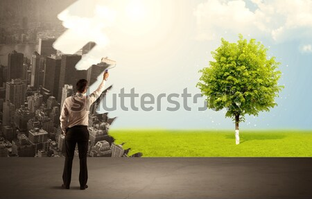 Salesman painting tree instead of city Stock photo © ra2studio