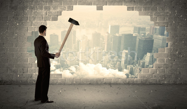 Business man hitting wall with hammer on city view Stock photo © ra2studio