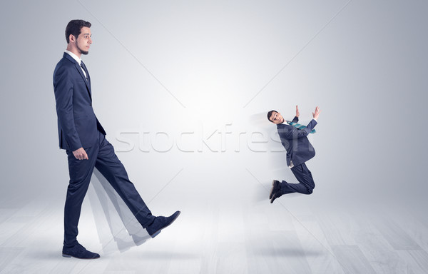 Giant businessman kicking out little businessman  Stock photo © ra2studio