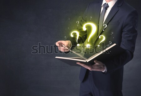 Businessman looking in a book. Stock photo © ra2studio