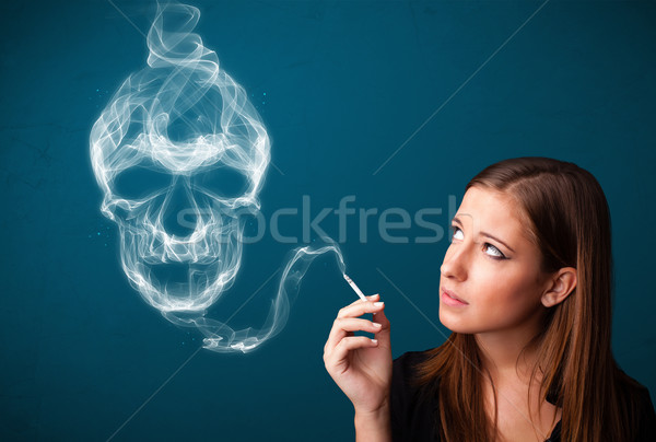 Stock photo: Young woman smoking dangerous cigarette with toxic skull smoke
