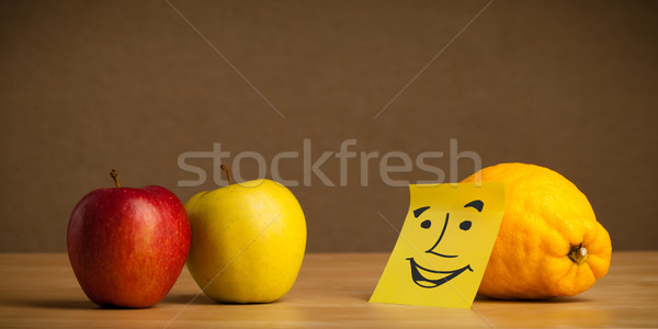 Stock photo: Lemon with post-it note smiling at apples