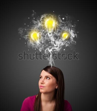 Thoughtful woman with smoke and lightbulbs above her head Stock photo © ra2studio