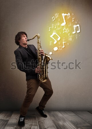 Bonito músico jogar saxofone notas musicais jovem Foto stock © ra2studio
