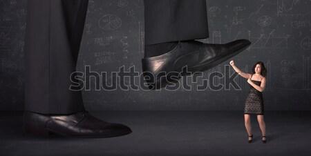 Huge leg stepping on a tiny businnesswoman concept Stock photo © ra2studio