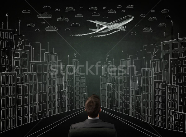 Young businessman sitting in an office chair and looking on a sketched cityscape drawing on a chalkb Stock photo © ra2studio