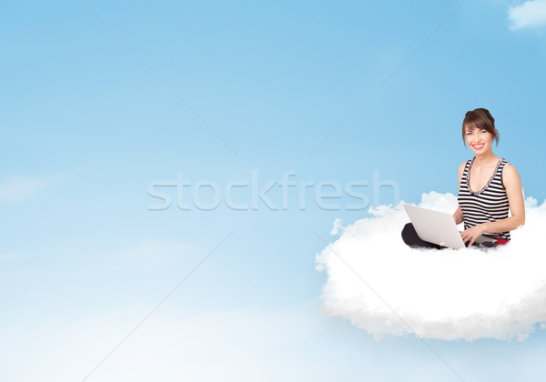 Young woman with laptop sitting on cloud with copy space Stock photo © ra2studio