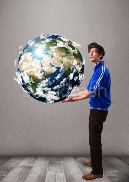 Good-looking man holding 3d planet earth Stock photo © ra2studio