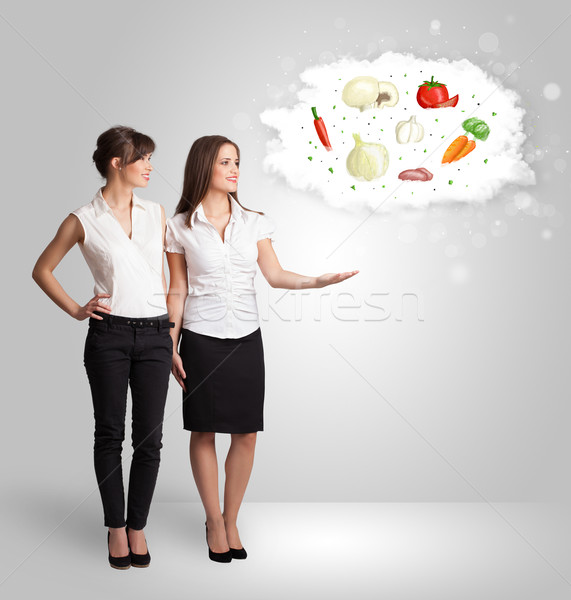 Pretty woman presenting a cloud of healthy nutritional vegetable Stock photo © ra2studio