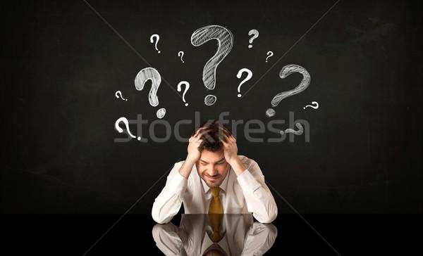 Sitting businessman under question marks Stock photo © ra2studio