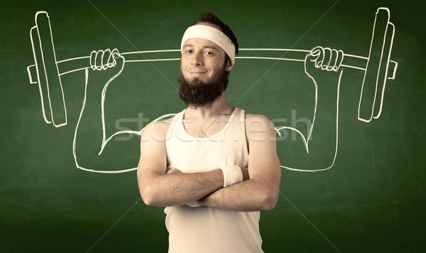 Young man lifting weight Stock photo © ra2studio