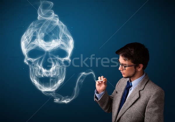 Young man smoking dangerous cigarette with toxic skull smoke Stock photo © ra2studio