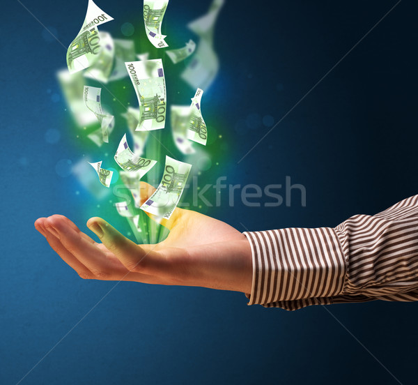 Glowing money in the hand of a businessman Stock photo © ra2studio