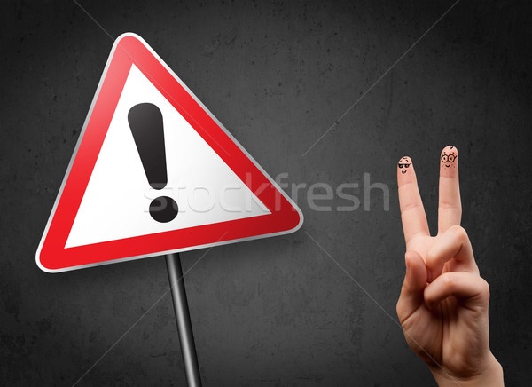 Happy cheerful smiley fingers looking at triangle warning sign with exclamation mark Stock photo © ra2studio