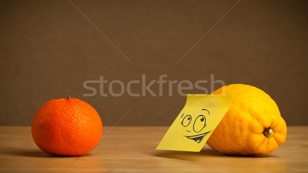 Lemon with post-it note looking curiously at orange Stock photo © ra2studio