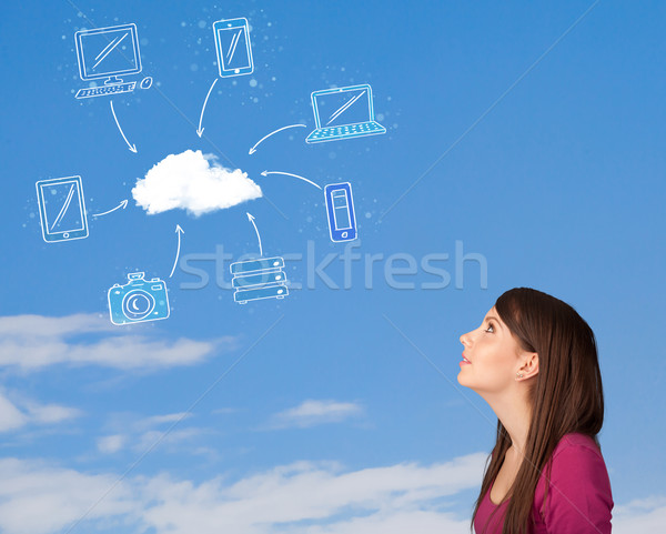 Stock photo: Casual girl looking at cloud computing concept on blue sky