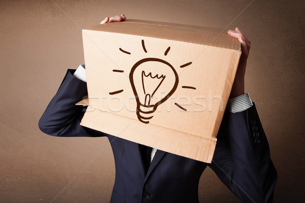 Businessman gesturing with a cardboard box on his head with ligh Stock photo © ra2studio