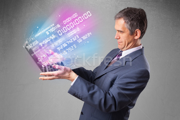 Businessman holding notebook with exploding data and numbers Stock photo © ra2studio