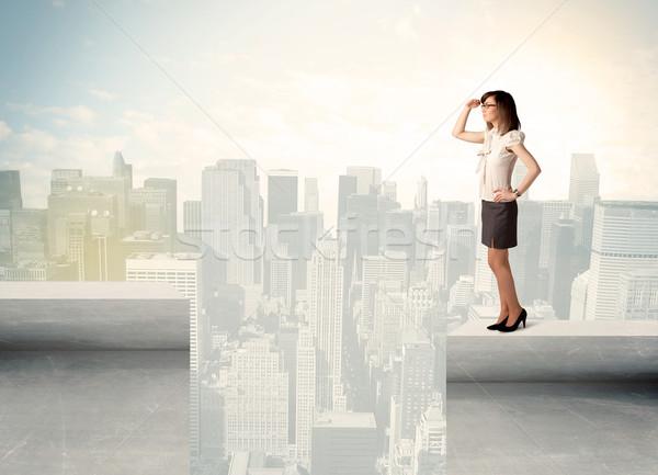 Businesswoman standing on the edge of rooftop Stock photo © ra2studio