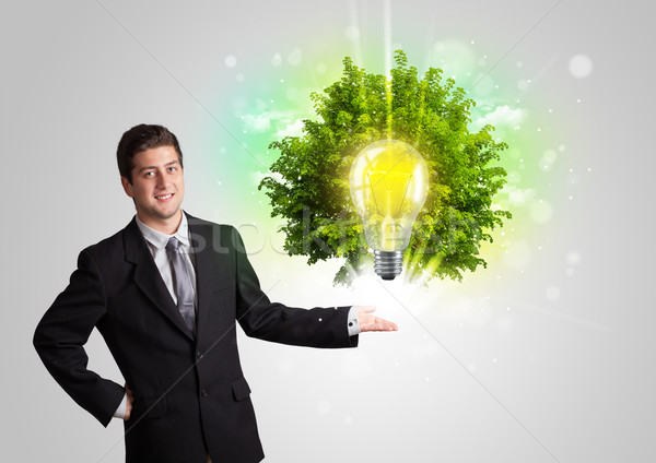 Young man presenting idea light bulb with green tree  Stock photo © ra2studio
