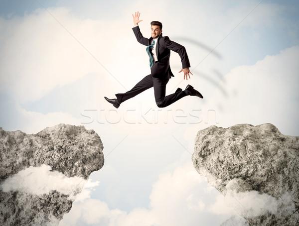 Heureux homme d'affaires sautant falaise affaires homme Photo stock © ra2studio