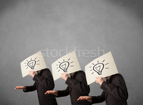 Men in suit gesturing with sketched lightbulbs on cardboard Stock photo © ra2studio