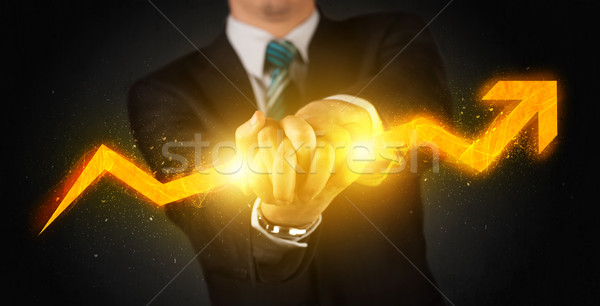 Business person holding a hot glowing upright arrow Stock photo © ra2studio