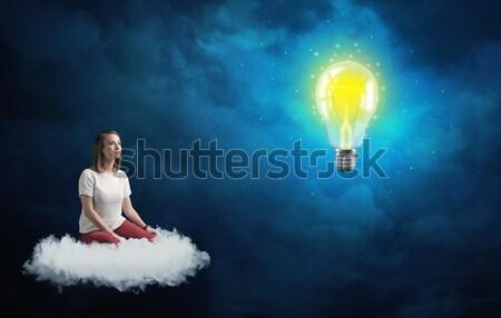 Woman sitting on a cloud lokking at huge lightbulb Stock photo © ra2studio