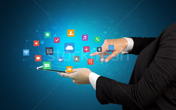 Hand holding tablet and application icons above Stock photo © ra2studio