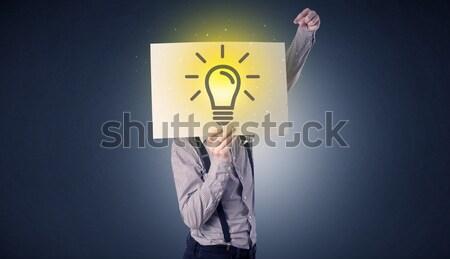 Businessman holding paper with lightbulb Stock photo © ra2studio
