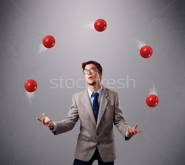young man standing and juggling with red balls Stock photo © ra2studio