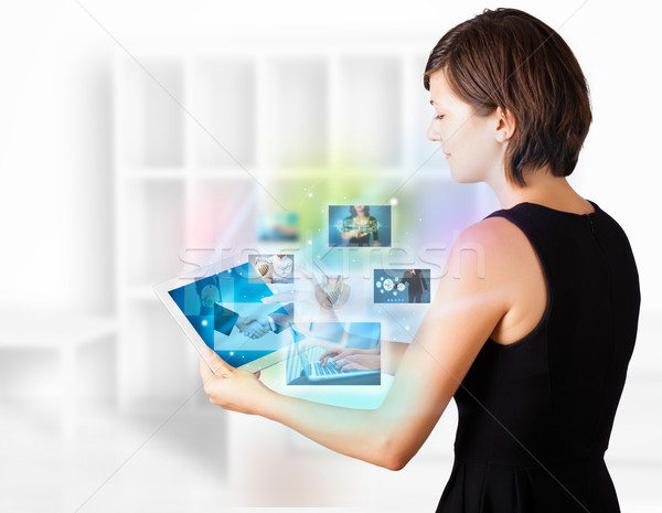 Young woman browsing pictures on modern tablet Stock photo © ra2studio
