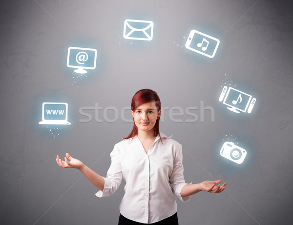 pretty girl juggling with elecrtonic devices icons Stock photo © ra2studio