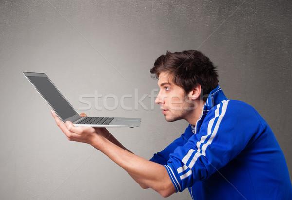 Attractive man holding modern notebook Stock photo © ra2studio