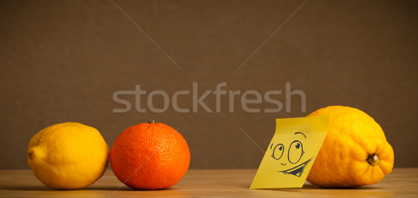 Lemon with post-it note looking curiously at citrus fruits Stock photo © ra2studio