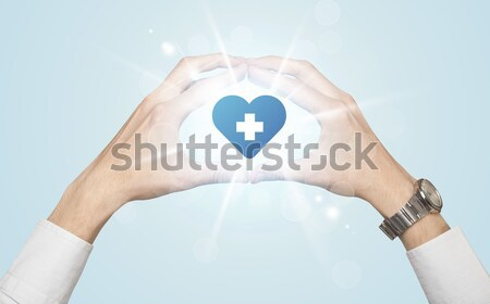 Hands creating a form with heart blue cross Stock photo © ra2studio