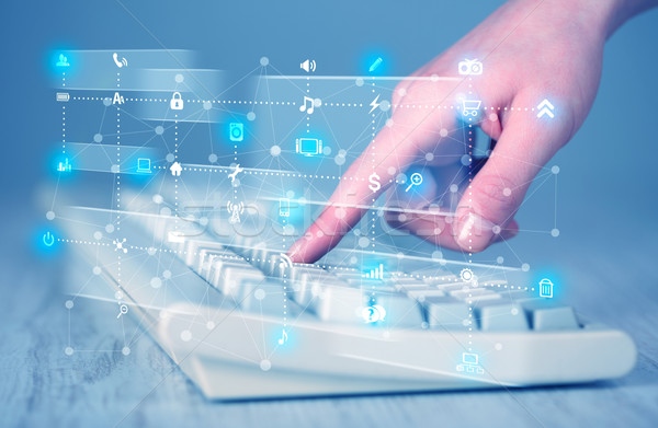 Hand pressing keyboard with high tech media icons Stock photo © ra2studio